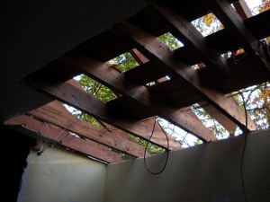 looking up through livingroom ceiling and roof at the sky and trees outside