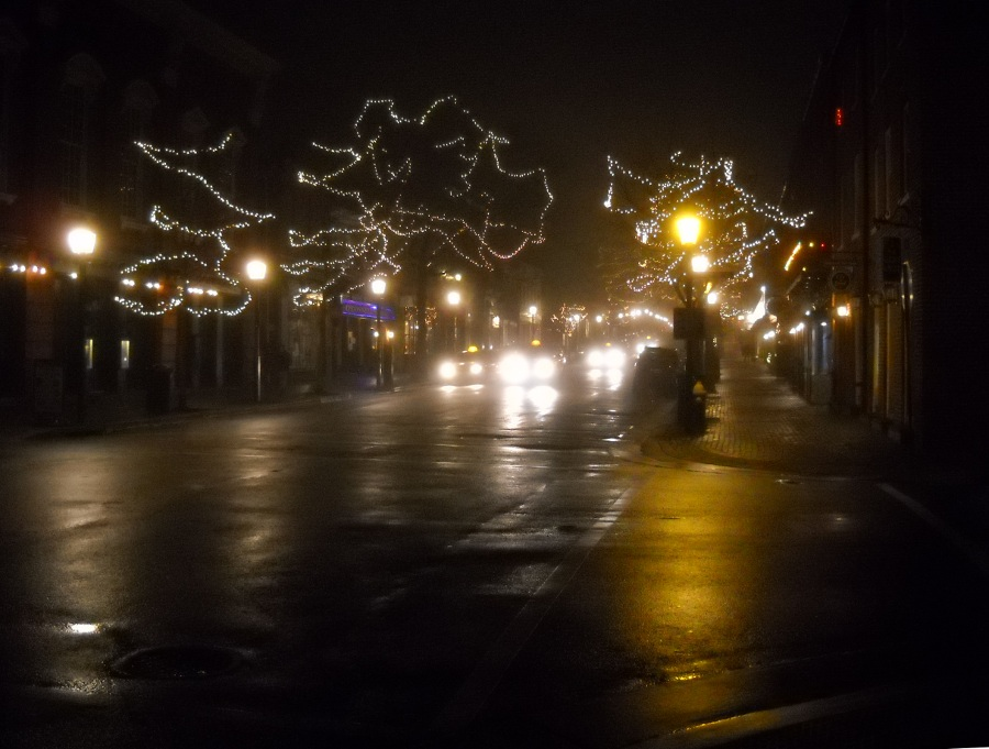 cold, foggy city street at night with christmas lights in trees