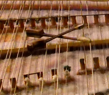a close-up of the dulcimer hammers sitting on the strings above the snow-covered dulcimer