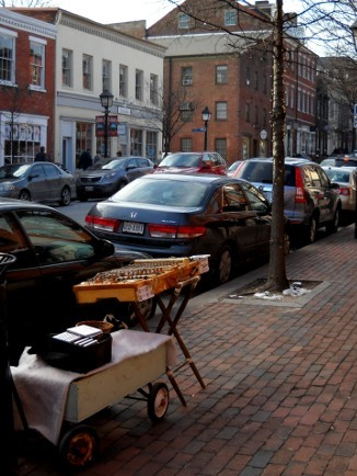 the dulcimer, set up on the street, a view past it to the parked cars and buildings behind it