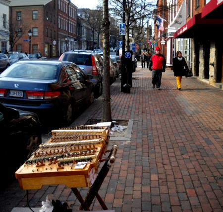 dulcimer set up with people walki down the street