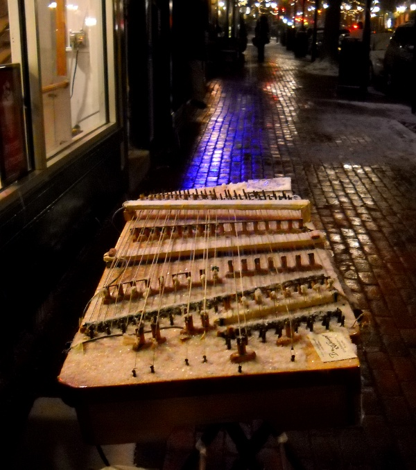 snow-coverd dulcimer at night with many colered city lights reflecting off wet brick sidewalk