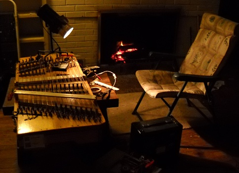 working on the dulcimer in front of the fireplace