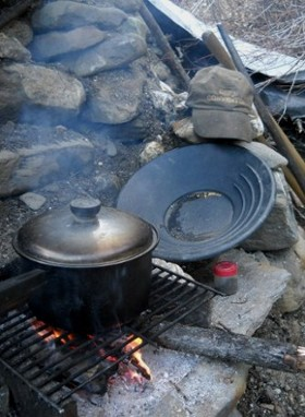 hearth at dig with cooking pot, gold in pan, and hat