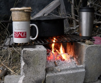 All the world's a stage coffee cup on crude hearth with coffee filter, saucepan, fire, and snow