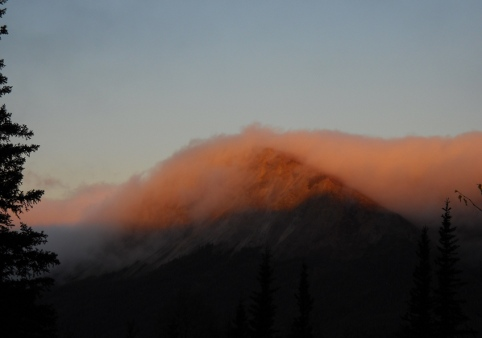 clouds flowing over a mountain like a wave, lit by the sunrise