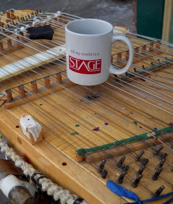 All My World's a Stage coffee cup sitting on the dulcimer with new year's confetti
