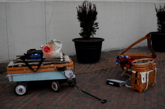 the dulci on the street on its wagon  sitting next to the harp and gear of another streetperformer