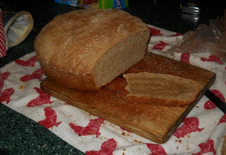 fresh, home-made bread, sliced open on the cutting board with an oiled slice waiting.
