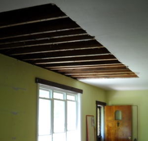the damaged ceiling torn out in a big, clean opening, showing the rafters