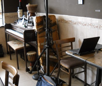 the dulci leaning against the piano inside the Epicure cafe, my stuff on a table by it
