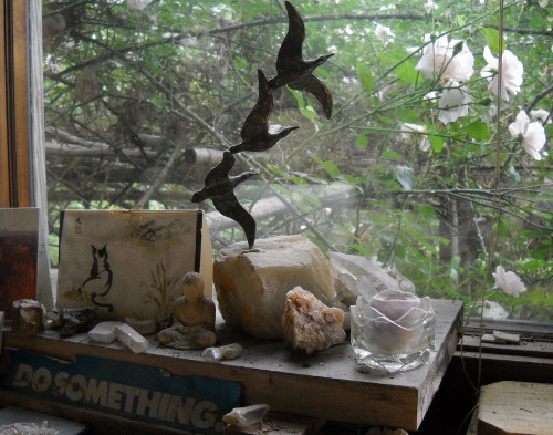 statue of buddha with sculpture of geese in flight and clipping that says Do Something, all on my desk