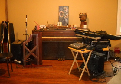 The music area in the house, the piano surrounded by instruments and gear