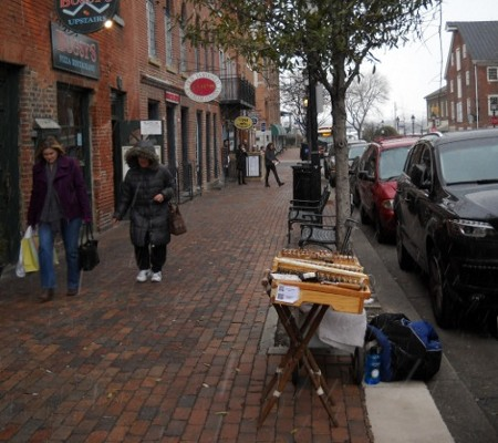 dulcimer set up on the street with snow falling and people walking in winter coats