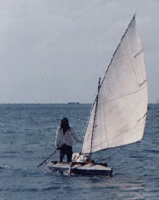 brian sailing his small open sailing kayak Horse, standing in white tropical pajamas, with his white wolf-dog on deck