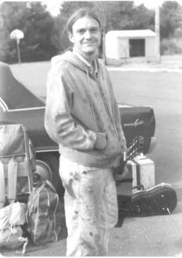 brian in 1981 in a coffeehouse parking lot with guitar in hand and reel to reel in a packing box in background