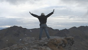 me, standing on a mountaintop facing away. arms extended out and up